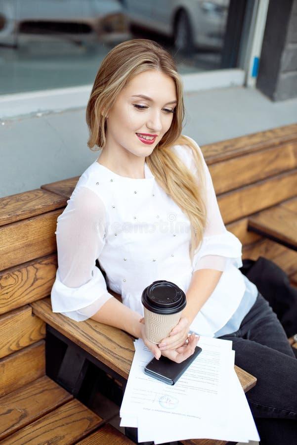 Papier de lecture de femme d'affaires en café pendant la pause de midi La femme d'affaires lit et souligne des notes dans un nouv image libre de droits