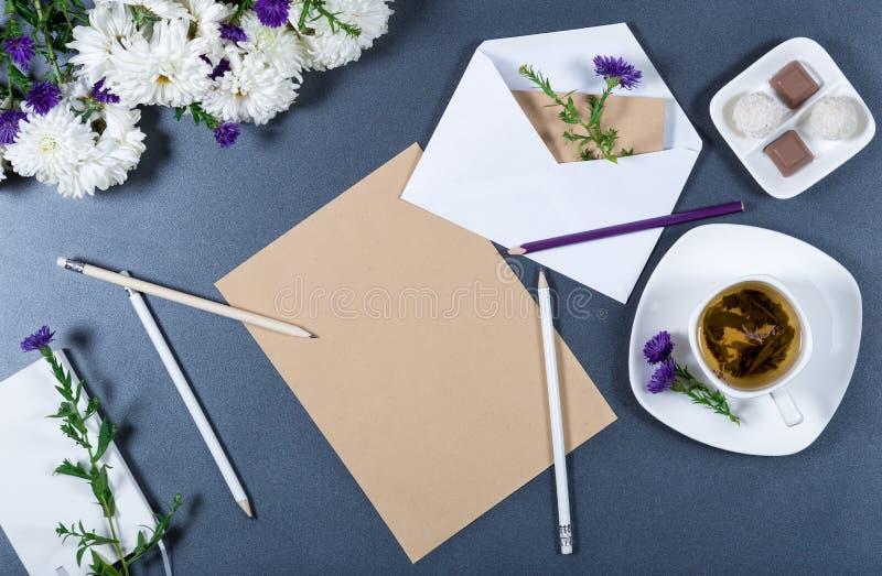 Papier de métier de Brown, chrysanthèmes frais, crayons, enveloppe avec photographie stock