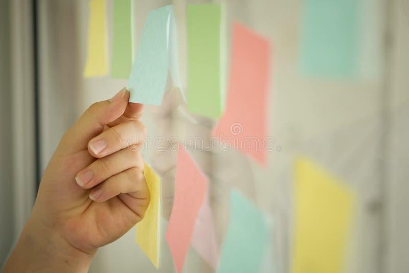 Papier de note collant sur la fenêtre, note de post-it d'utilisation d'homme d'affaires photographie stock libre de droits