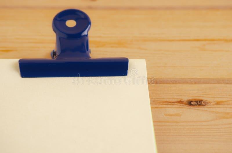 Papier de note vide avec le trombone sur le bureau en bois photos stock