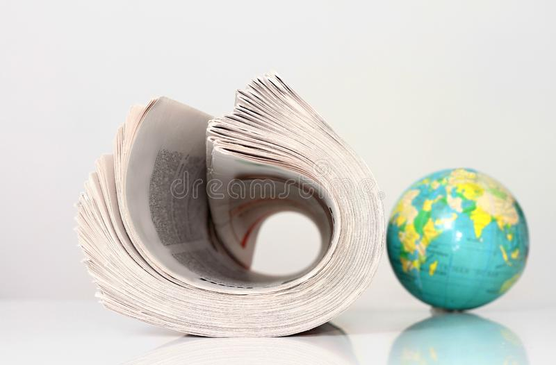 Papier de nouvelles avec le globe sur une table image stock