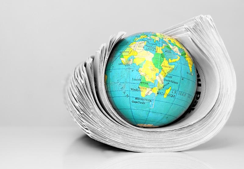 Papier de nouvelles avec le globe sur une table photographie stock