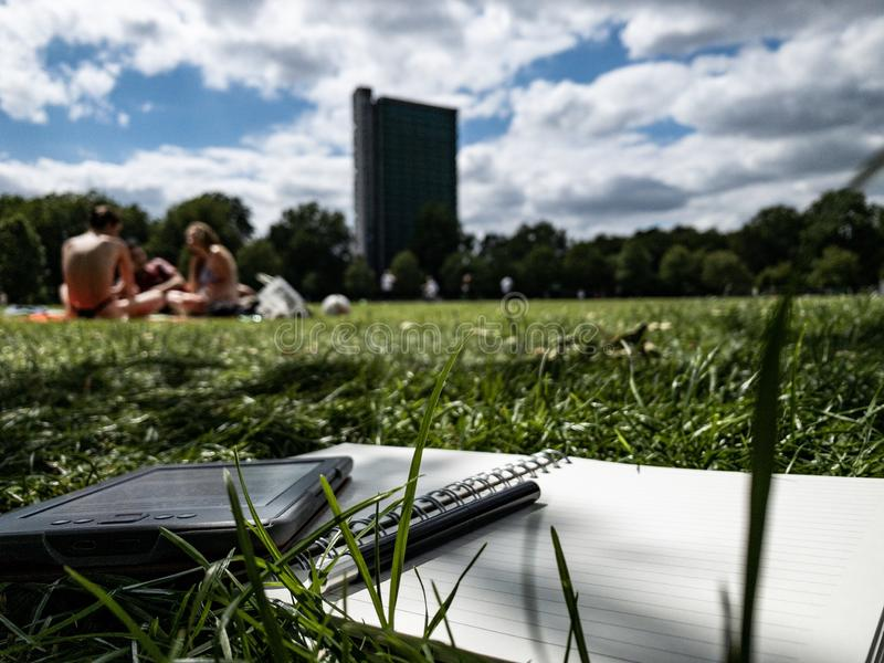 Papier de stylo et lecteur d'ebook sur l'herbe images libres de droits