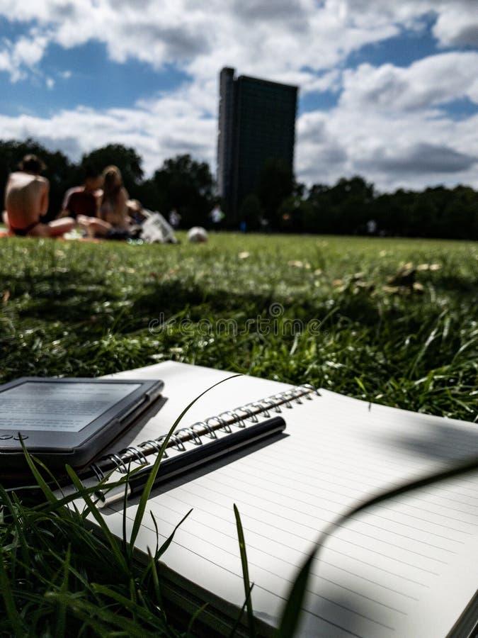 Papier de stylo et lecteur d'ebook sur l'herbe photo stock