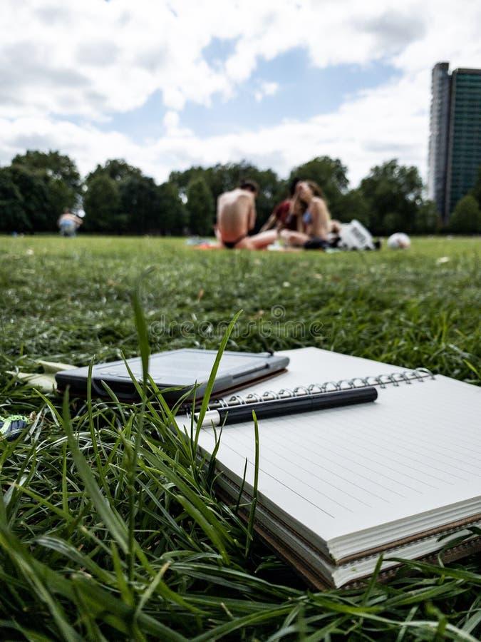 Papier de stylo et lecteur d'ebook sur l'herbe image stock