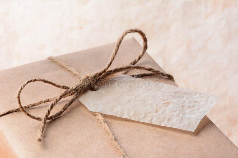 In Papier eingewickeltes Paket Browns mit Geschenk-Tag lizenzfreie stockbilder