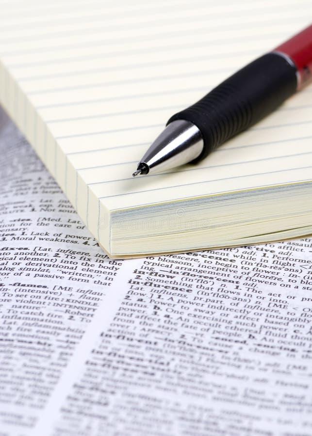 Papier et crayon lecteur sur le dictionnaire images libres de droits