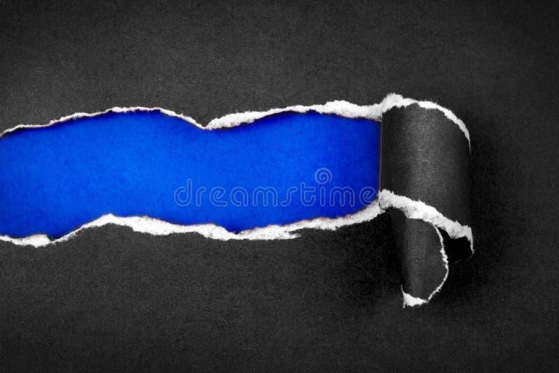 Papier et espace noirs déchirés avec le fond de papier bleu de ciel, blac photo stock