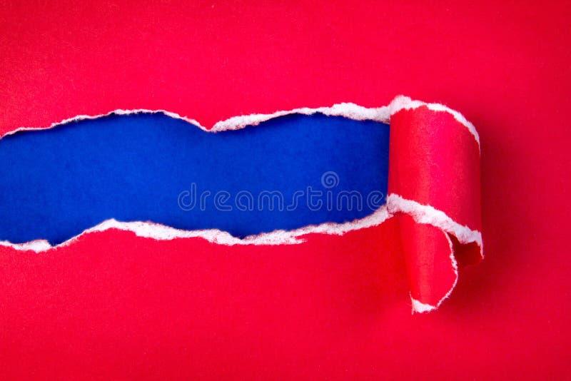 Papier et espace rouges déchirés pour le texte avec le fond de papier bleu photo stock