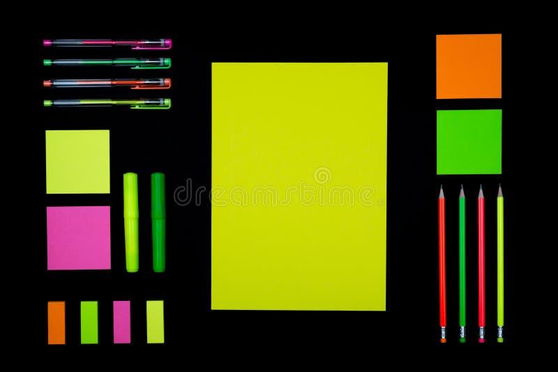 Papier et papeterie au néon sur le noir images libres de droits