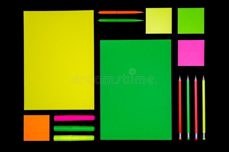 Papier et papeterie au néon sur le noir photos libres de droits