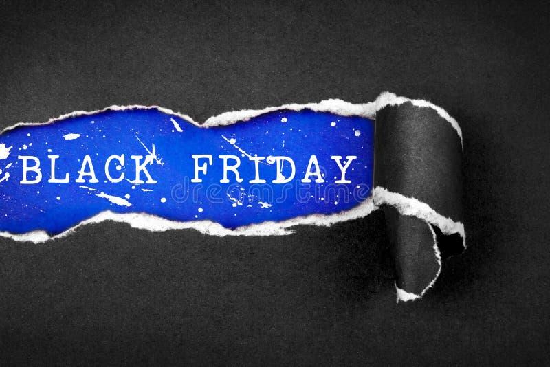 Papier et texte noirs déchirés de BLACK FRIDAY avec le papier bleu de ciel de retour images libres de droits