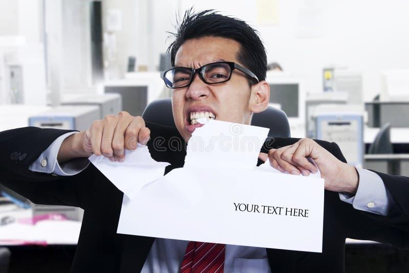 Papier fâché de larme d'homme d'affaires au bureau images libres de droits