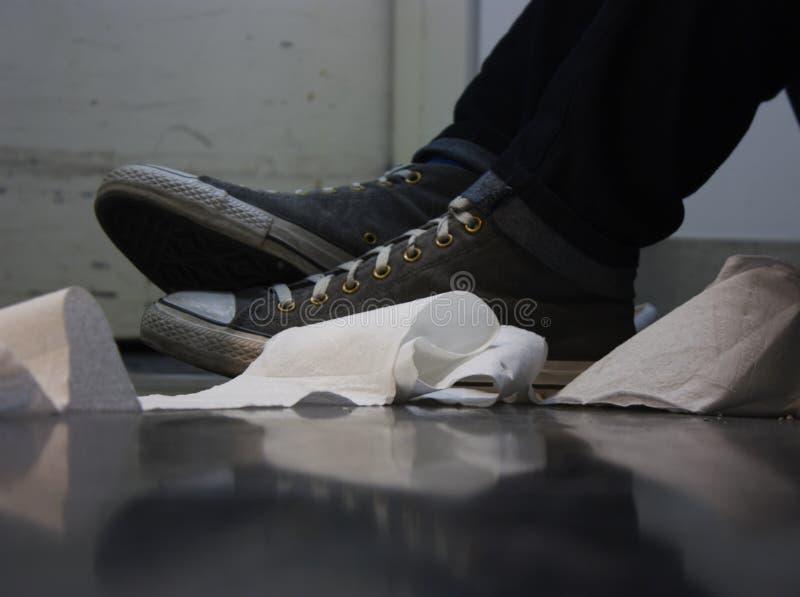 Papier hygiénique et chaussures sur le plancher photo stock