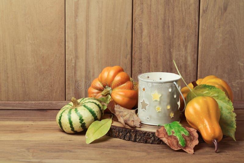 Papier peint d'automne avec la bougie, les décorations de potiron et les feuilles de chute Table de thanksgiving image stock