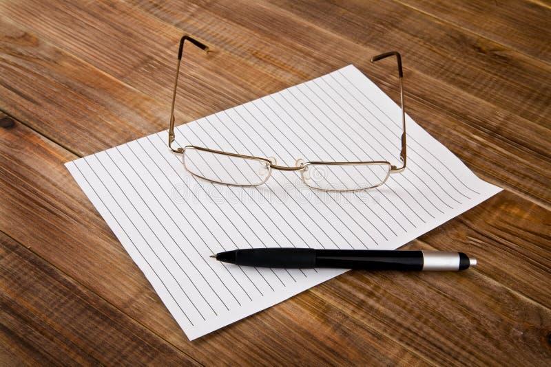 Papier, Stift und Gläser stockbild