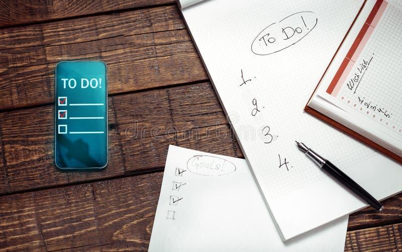 Papier und elektronisches Listen auf Holzoberfläche, Draufsicht tun Notiz-Planungs-Technologie-Konzept stockfotografie