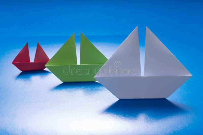 Papier versendet Segeln auf Meer des blauen Papiers. Origami-Boot. Papiermeer stockfotografie