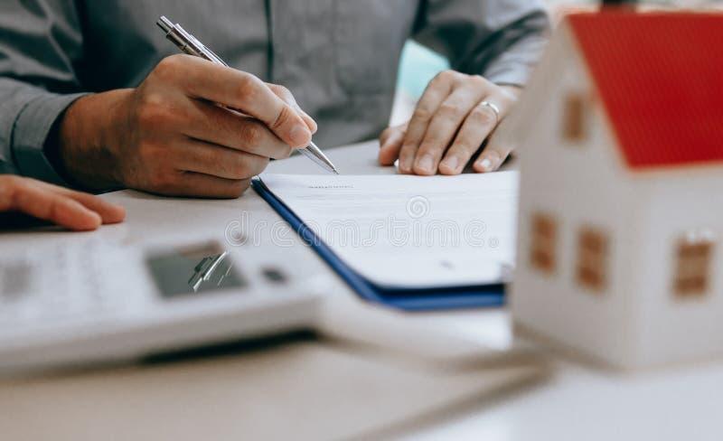 Papier-Vertragsvereinbarung des asiatischen Mannes unterzeichnende für Haus mit Musterhaus lizenzfreie stockfotografie