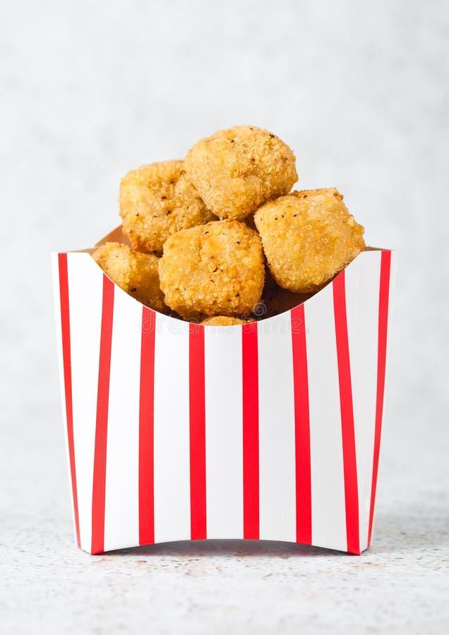 Papierbehälter mit gebratenem knusperigem Hühnerpopcorn lizenzfreies stockfoto