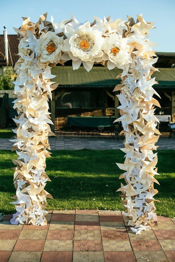 Papierblumen im Hochzeitsdekor, Luxushochzeitsdekorationen für Zeremonie Hochzeitsbogen stockfotos