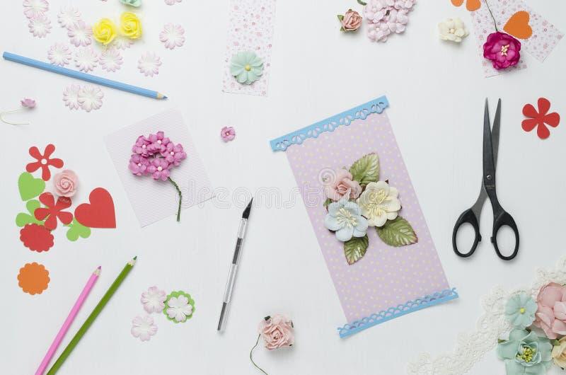 Papierblumen, Scheren und farbige Bleistifte auf weißem Hintergrund Scrapbooking lizenzfreie stockbilder