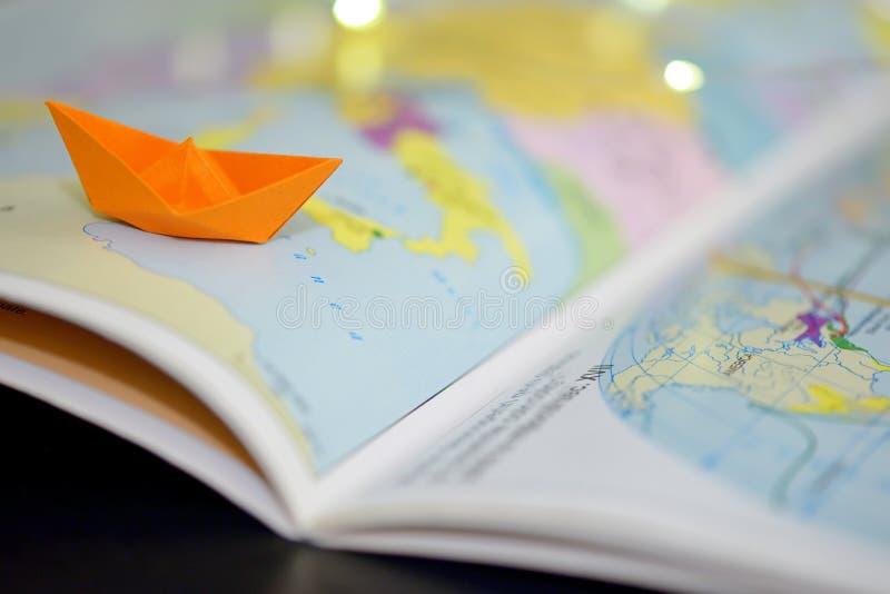 Papierboot auf einem Atlasbuch lizenzfreie stockfotos