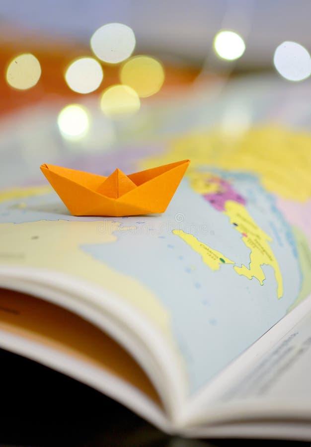 Papierboot auf einem Atlasbuch lizenzfreies stockbild