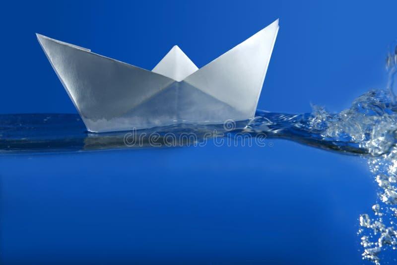 Papierboot, das über blaues reales Wasser schwimmt stockfotos