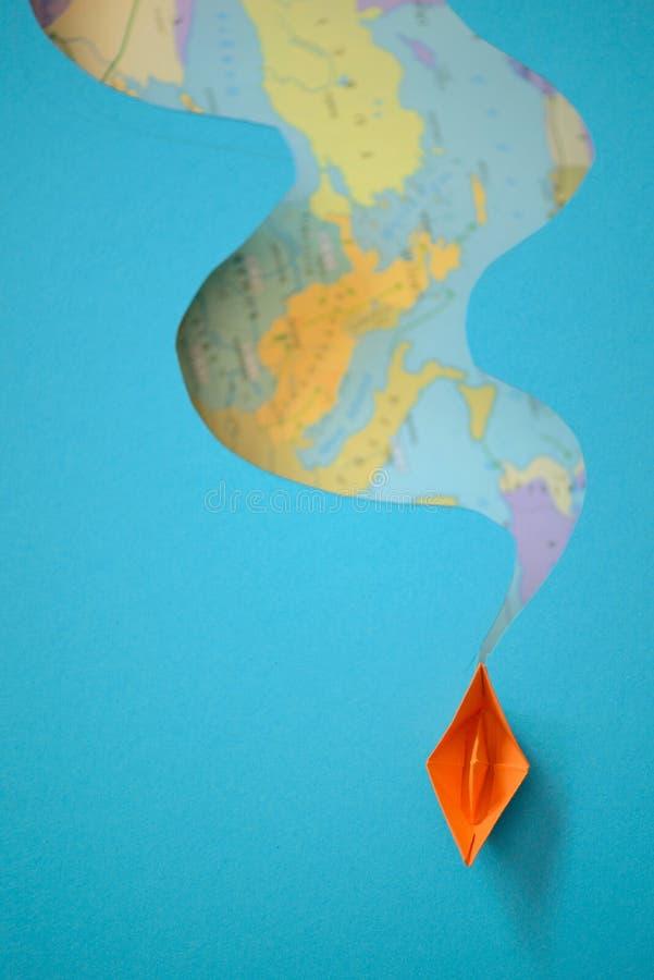 Papierboot, das Wellen auf einer Papierhintergrundkarte macht stockfotografie