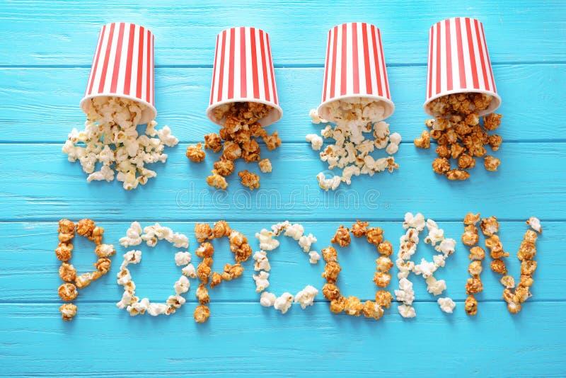 Papiereimer und Wort machten vom geschmackvollen Popcorn auf hölzernem Hintergrund lizenzfreies stockbild