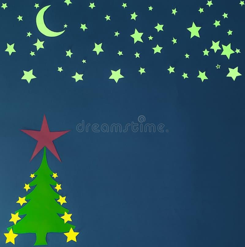 Papieren kerstboom met gele maan en sterren stock afbeelding