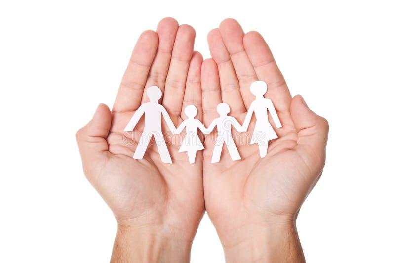 Papierfamilie in den Händen lizenzfreies stockfoto