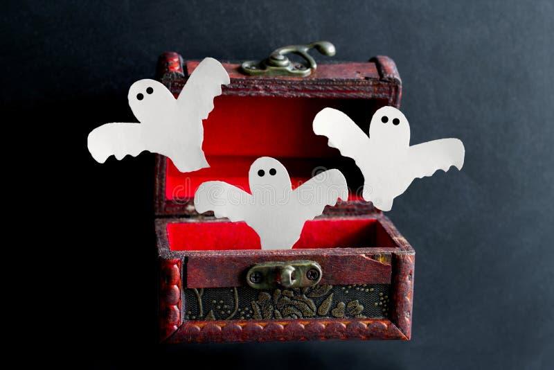 Papiergeister fliegen aus einem hölzernen Kasten der alten Weinlese auf einem schwarzen Hintergrund, festliche Halloween-Karte he lizenzfreie stockbilder