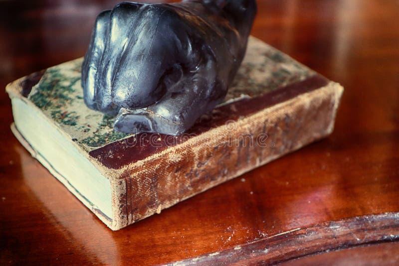 Papiergewicht der Weinlese mögen eine menschliche Faust auf Buch lizenzfreie stockfotografie
