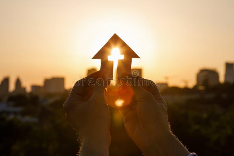Papierhaus mit Kreuz in der Hand lizenzfreies stockfoto