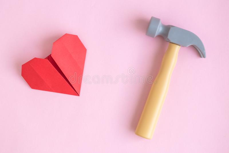 Papierherz- und Hammerspielzeug auf rosafarbener Hintergrundzusammenfassung stockbild