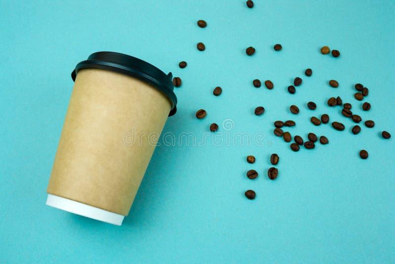 Papierkaffee zum mitnehmen-Schalen-Kaffeebohnen auf blauem Hintergrund stockbild