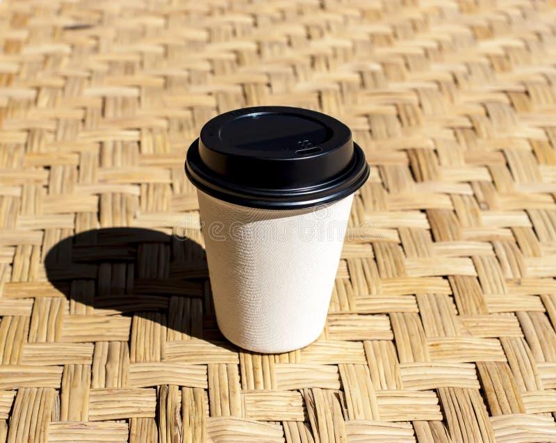 Papierkaffeetasse setzte an Rattanmatte gegen das Morgenlicht stockfotografie