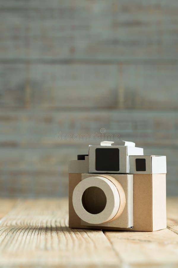 Papierkamera auf dem hölzernen Hintergrund stockfoto