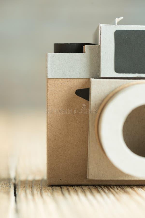Papierkamera auf dem hölzernen Hintergrund stockfotos
