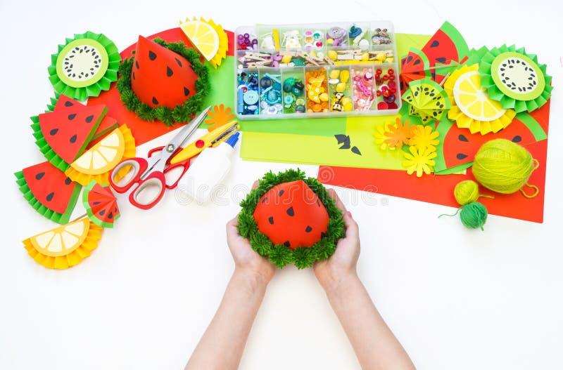 Papierkappe diy für Fruchtpartei Wassermelonen-Geburtstag Die Hände der Kinder machen Handwerk stockfoto