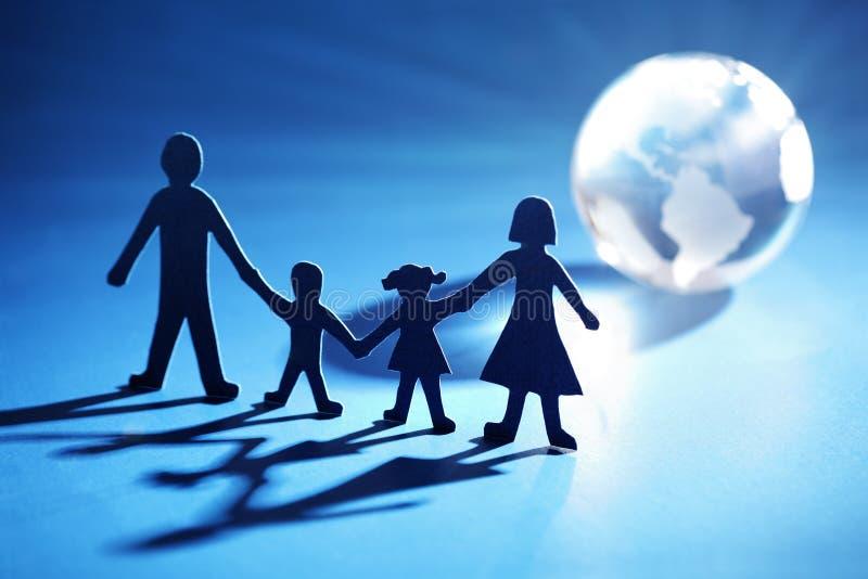 Papierkettenfamilie, die in Richtung zur Leuchte sich bewegt stockfoto
