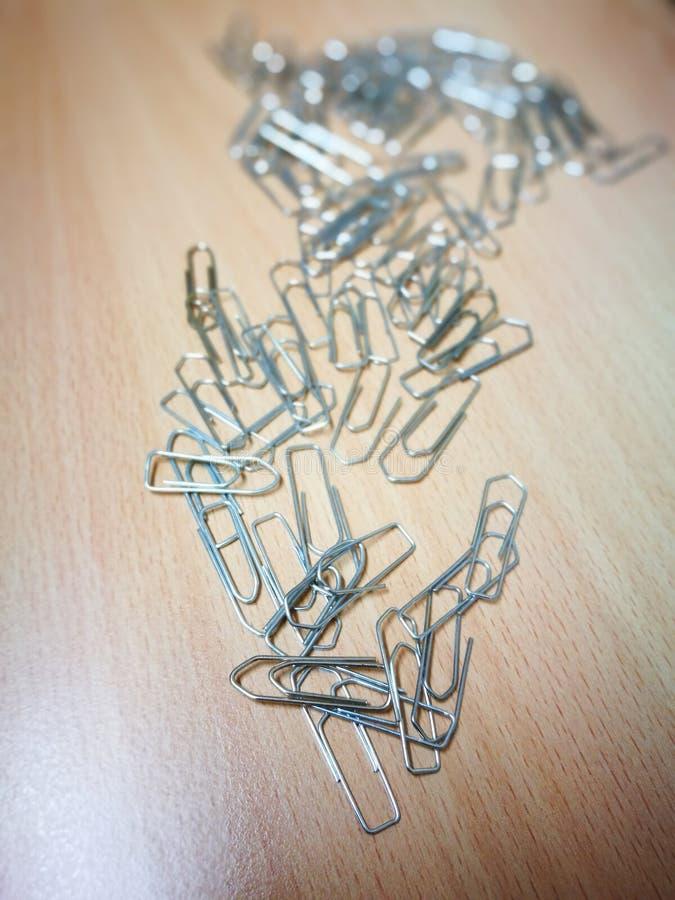 Papierklammern, die auf einem hölzernen Schreibtisch liegen stockfotos