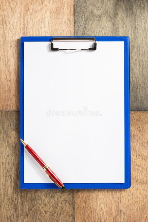 Papierklemmbrett am hölzernen Hintergrund lizenzfreie stockfotografie