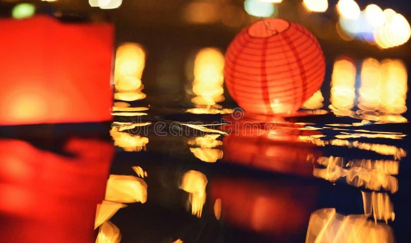 Papierlaternen, die in Wasser nachts schwimmen lizenzfreies stockfoto