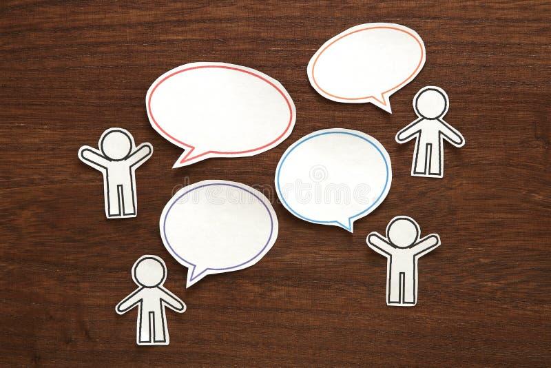 Papierleute mit bunter leerer Dialogrede sprudeln auf braunem Holz schwarzes Telefon mit Empfänger stockfoto