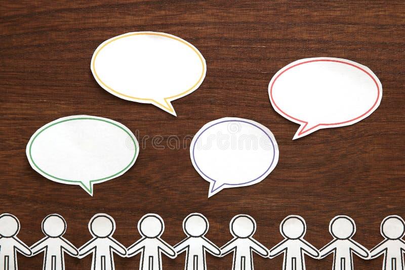Papierleute mit bunter leerer Dialogrede sprudeln auf braunem Holz schwarzes Telefon mit Empfänger lizenzfreies stockbild