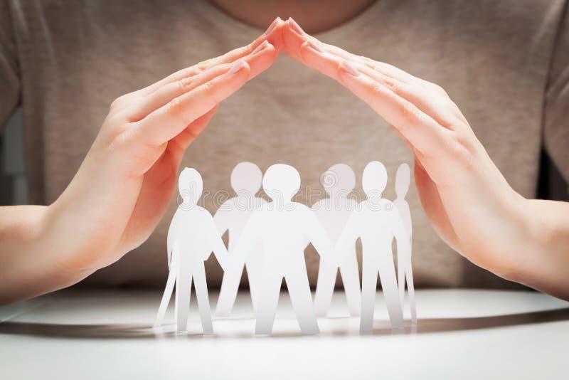 Papierleute unter Händen in der Geste des Schutzes stockbilder