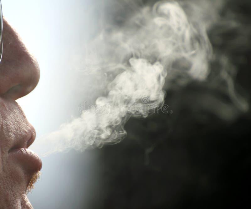 Papierosu dymu komes z usta palacza mężczyzna obrazy royalty free